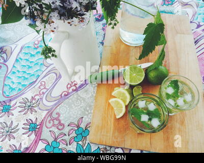 Hohe Betrachtungswinkel von Mojito auf Schneidebrett von Blumenvase auf dem Tisch