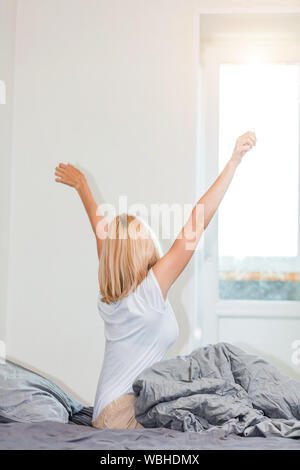 Hintere Aufnahme Ob blond europäische Frau aufwachen und Stretching im Bett mit Händen, starten neuen Tag für gesunden Schlaf. Erwachen, guten Morgen, - Stockfoto
