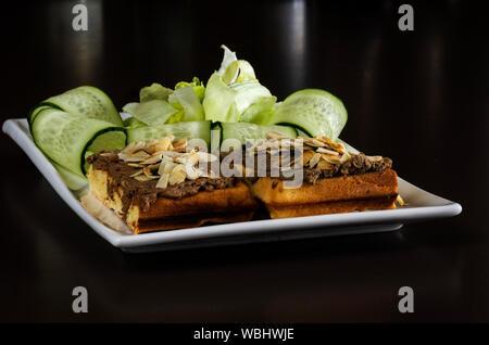 In der Nähe des Belgischen Waffeln serviert mit Mandeln und Gurke in Fach auf Schwarz Tabelle - Stockfoto