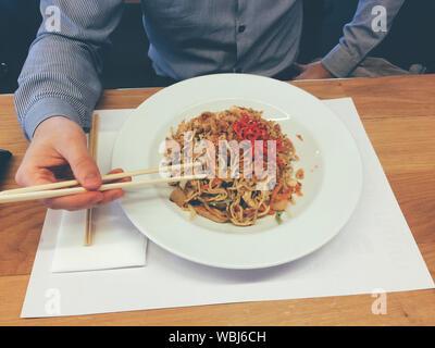 Mittelteil der Mann isst Nudeln am Tisch - Stockfoto