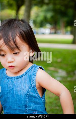 Asiatische 1 Jahr altes Kleinkind besetzt ist, spielen in einem tropischen Park am Morgen. - Stockfoto