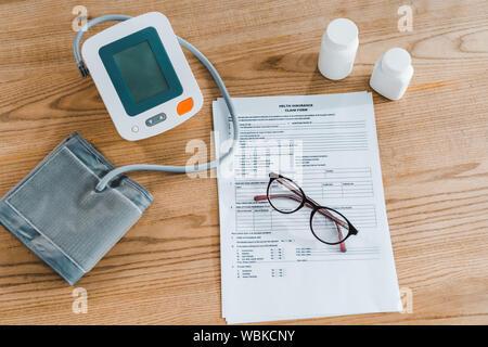 Blick von oben auf den Blutdruck überwachen in der Nähe von Dokument und Gläser - Stockfoto