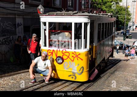 Touristische posiert vor einem Graffiti bedeckt Standseilbahn Straßenbahn, Lissabon, Portugal. - Stockfoto