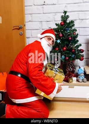 Portrait von Santa mit Geschenk von Weihnachten zu Hause - Stockfoto