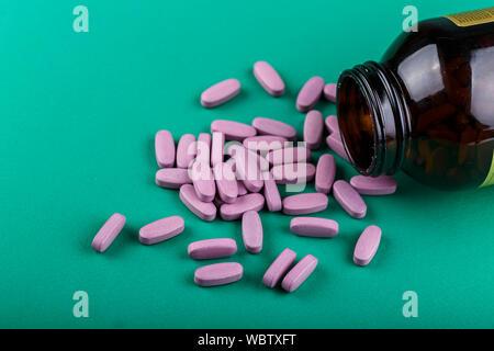 Organische homöopathische Pillen auf grünem Hintergrund verstreut. Platz für Text - Stockfoto