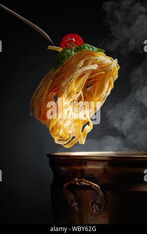 Hausgemachte rohes Ei Nudeln und altes Messing Topf mit heißem Wasser. Schwarzen Hintergrund. Kopieren Sie Platz. - Stockfoto