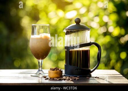 Selektiver Fokus auf Französische Presse Kaffeekanne und hausgemachte Eiskaffee, faulen Sonntag Morgen oder Abend mit kühlen Eiskaffee im Haus Garten, brechen. Werden - Stockfoto