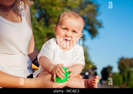 Baby Mädchen mit Spielzeug spielen Sitzen auf den Knien ihrer Mutter im Sommer Park. Familie Spaß im Freien. Kleinkind sieht an Kamera - Stockfoto