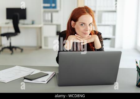 Junge Managerin geben eine gewagte Lächeln, als sie ihr Kinn auf ihre Hände hinter dem Schreibtisch im Büro liegt, als sie einen neuen Plan formuliert - Stockfoto
