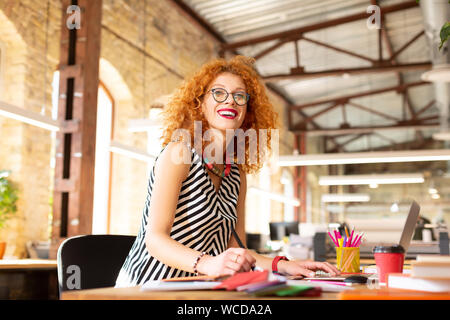 Strahlende rothaarige Frau trinkt Kaffee und Arbeiten - Stockfoto