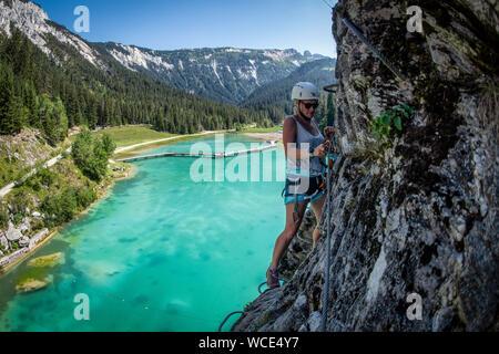 Eine Frau steigt der Klettersteig über Lac de la Rosière in der Nähe der Französischen Courchevel in den Alpen im Sommer.