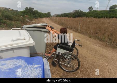 Behinderte Mädchen im Rollstuhl im Alltag tun, Recycling - Stockfoto