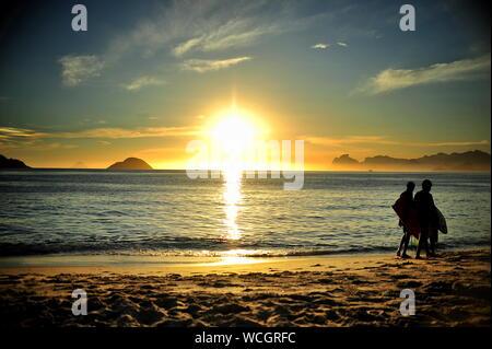 Silhouette Menschen zu Fuß am Strand gegen Himmel bei Sonnenuntergang - Stockfoto