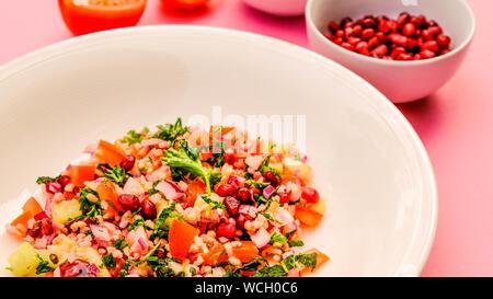 Libanesischen Stil vegetarische Tabbouleh Salat mit Bulgur weizen, Granatapfel, Tomaten und Gurken - Stockfoto
