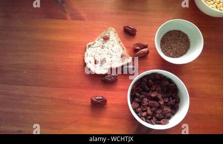 Schüssel mit Rosinen, Leinsamen, Feigen und anderen getrockneten Früchten in weißen Schalen - Stockfoto