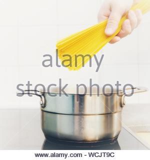 Nahaufnahme einer Hand, die Spaghetti über Utensil gegen die Wand - Stockfoto