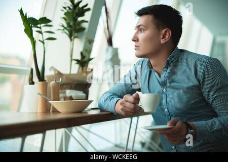 Junge gut aussehender Geschäftsmann seine heißen Kaffee trinken und essen Salat zum Mittagessen während der Pause bei angesagten Cafes in der Nähe von Büro. - Stockfoto