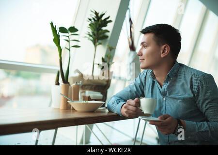 Jungen hübschen Lächeln, Geschäftsmann seine heißen Kaffee trinken und essen Salat zum Mittagessen während der Pause bei angesagten Cafes in der Nähe von Büro. - Stockfoto