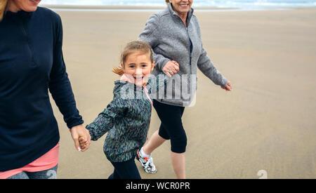 Verspielte Frau gehen mit Mutter und Tochter am Strand - Stockfoto