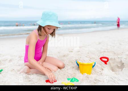 Glückliches Kind Mädchen spielen mit Sand am Strand im Sommer - Stockfoto