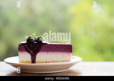 Blueberry Mousse Kuchen gekrönt mit frischen Blaubeeren und Minzeblättchen. - Stockfoto