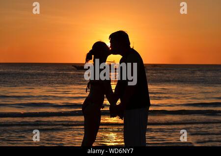 Silhouette Paar Küssen beim Stehen auf Ufer am Strand bei Sonnenuntergang Stockfoto