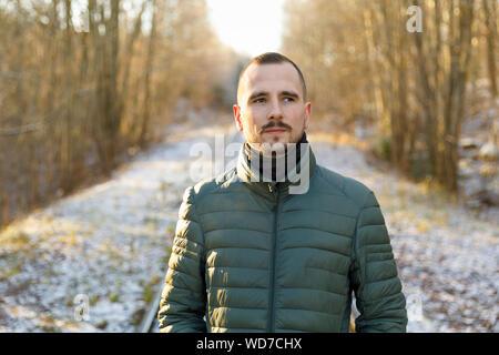 Jungen Mann mit grünen Puffer Jacke auf verschneiter Straße durch den Wald - Stockfoto