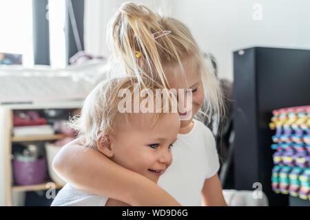Cute adorable Blonde caucaian kleine Schwester ihren Toddler Bruder umarmte. paar fröhliche Geschwister spielen Indoor. Süße Mädchen und Jungen genießen Stockfoto
