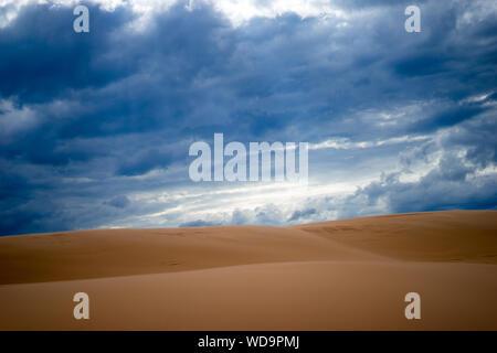 Sanddünen gegen bewölkten Himmel in der Wüste - Stockfoto