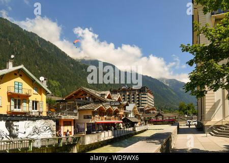 Malerische Aussicht der alpinen Stadt Chamonix-Mont-Blanc mit dem Fluss Arve und ein Gleitschirm im Flug über der Französischen Alpen, Haute Savoie, Frankreich - Stockfoto