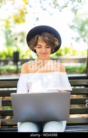 Lächelnden jungen Frau Arbeiten am Laptop sitzt auf der Bank im Park und Kaffee. - Stockfoto