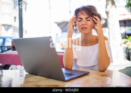 Junge Frau mit Kopfschmerzen am Tisch sitzen