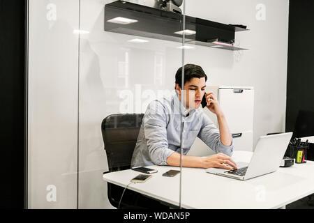 Junger Mann mit Laptop, während Sie ein Telefongespräch - Stockfoto