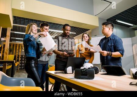 Junge Menschen software programmierer Testen einer neuen Apps mit 3D virtual reality Brillen, Notebooks und Tablet-PCS im Büro - Stockfoto