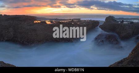 Wasser fließt von Felsformationen an wenig Corona Strand bei Sonnenuntergang - Stockfoto