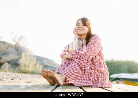 Junge Frau tragen geprüft Kleid umarmte ihre Knie - Stockfoto