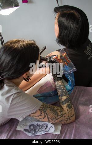 Charkow, Ukraine - April 08, 2017: Nahaufnahme der Hand eines tattoo Master in schwarz Handschuhe mit einem Tattoo Maschine macht ein Tattoo nach dem sketc - Stockfoto