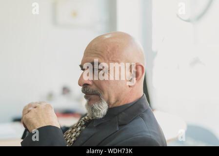 Reife älterer Mann denken im Büro im Bürogebäude im Innenbereich - Stockfoto