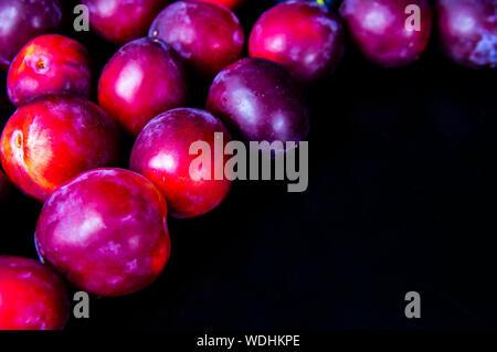 Früchte der Garten Pflaumen auf schwarzem Hintergrund. Für Text platzieren. Hintergrund. - Stockfoto