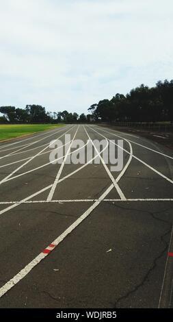 Weiße Linien auf der leeren Straße gegen den Himmel - Stockfoto