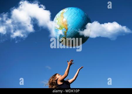 Junge Mädchen Fänge Planeten Erde. Glückliches Kind mit Globus in erhobenen Händen auf und blauer Himmel. Umwelt und Ökologie. Welt Eart - Stockfoto