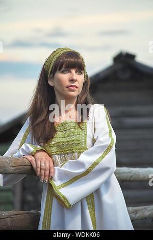 Schönen ruhigen Mädchen in weißen russische Tracht schaut weg, Kleid im Freien, vor dem Hintergrund eines alten Holzhaus - Stockfoto