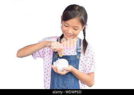 Portrait von kleinen asiatischen Mädchen holding Sparschwein auf weißem Hintergrund - Stockfoto