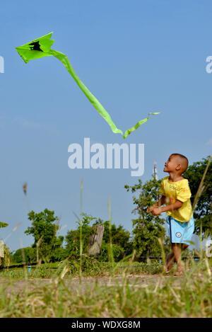 Volle Länge des Jungen fliegende Drachen über Feld gegen blauen Himmel - Stockfoto