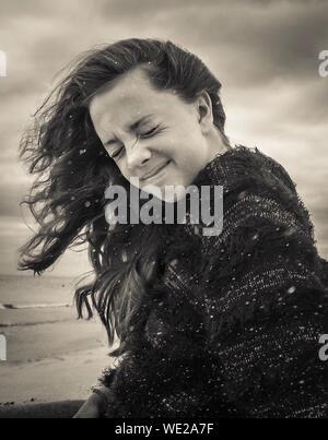 Junge Frau mit geschlossenen Augen am Strand bei windigem Wetter - Stockfoto