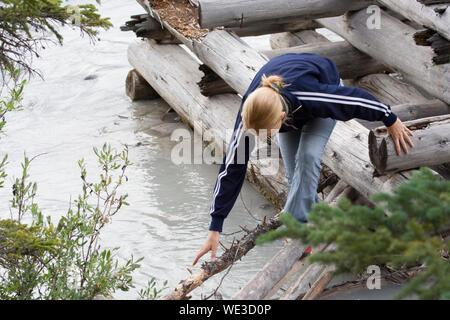 Hohe Betrachtungswinkel und der Frau zu Fuß auf Holzfloß am Fluss - Stockfoto