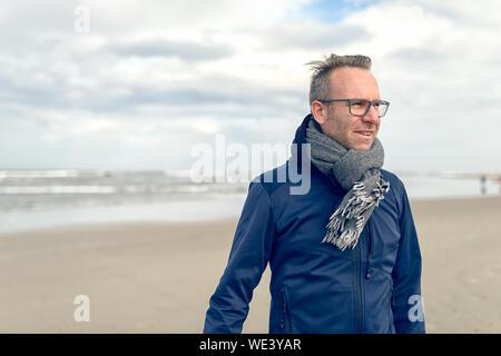 Irritierte Mann mittleren Alters Brille trägt und einen gestrickten Wollschal stehend auf einer einsamen Herbst Strand an einem bewölkten Tag mit Copy space - Stockfoto
