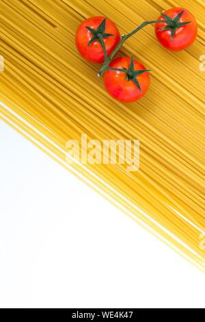 Hohe Betrachtungswinkel von Tomaten auf rohe Spaghetti auf weißem Hintergrund - Stockfoto