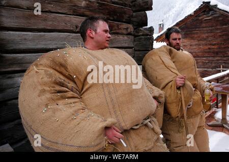 Schweiz, Wallis, Val d'Herens, Dorf Evolène, Karneval, die Vorbereitung des empailles (junge Männer mit alten Taschen gekleidet mit ca. 50 kg Stroh gefüllt) und tragen ein Lokal aus Holz geschnitzte Maske, die mythische und oft afraying Tiere - Stockfoto