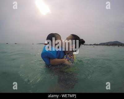 Seitenansicht der Mutter küssen Sohn beim Schwimmen im Meer gegen bewölkter Himmel - Stockfoto